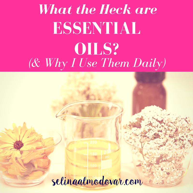 """A beaker of oil surrounded by various piles of flowers and a glass bottle in the background with pink overlay and white text that reads, """"What the Heck Are Essential Oils (and Why I Use Them Daily)"""""""